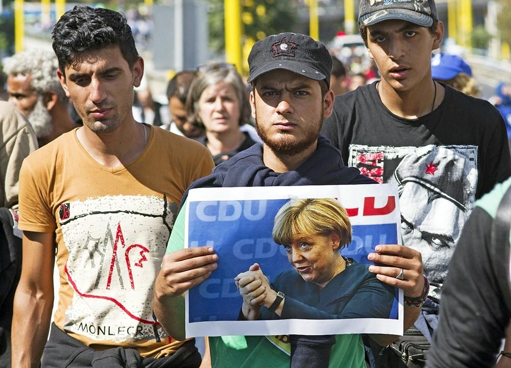Революции и беженцы связаны одной цепью с Европой — Беженцы с плакатом Меркель в руках
